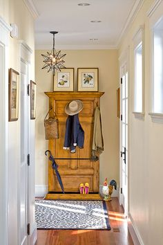 In this entry, a vintage door is repurposed as a backing for coat hooks; a length of pipe cleverly corrals umbrellas. Crown molding trims out the top and bottom, where it forms a tray.