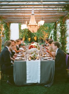 small, pretty florals, glasses & fruits balanced by beautiful, dramatic lighting. outside. long table. love everything