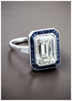 A gorgeous emerald cut diamond surrounded by a halo of Ceylon sapphires, and set in a beautiful platinum mounting. Such a wonderful antique engagement ring!