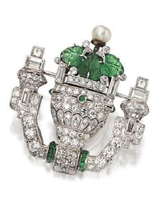 DIAMOND AND EMERALD WATCH-BROOCH, PAUL FLATO, CIRCA 1930. Designed as a flower-filled urn, set with baguette, round and single-cut diamonds weighing approximately 3.25 carats, accented further with carved and calibré-cut emeralds, the stem with a single pearl, vase swivels to reveal a watch dial, mounted in platinum, dial signed Flato