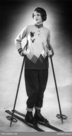 Modell i skidkläder. Stickad tröja med knappar och rutor, mörka byxor, raggsockor, pjäxor, tumvantar och basker. Står på ett par skidor. Fotograf: Erik Holmén, 1930