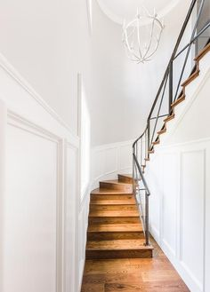 Chic winding staircase features an iron stair railing and wainscoted walls illuminated by a whitewashed chandelier.