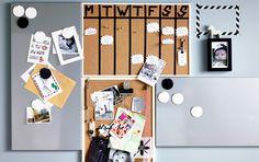 En samling korktavler og magnettavler arrangeret på en væg med en hjemmelavet kalender og postkort og breve sat på tavlerne