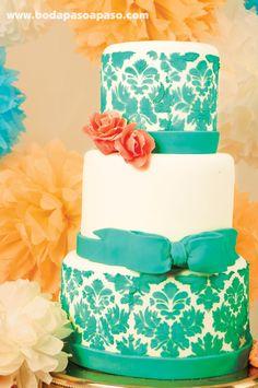 TOQUE ROMÁNICO - Hermoso y delicado pstel de tres tortas elaborado en fondant blanco como base, tonos pasteles, esmeralda y coral haciendo juego sobre el pastel. Pastelería Bom Bom.