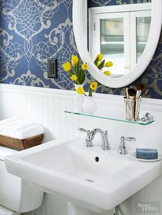 A pedestal sink fits the home's style but lacks storage, but a glass shelf and a new medicine cabinet stand in as handy storage. The homeowner suggests making sure the new cabinet will fit the existing hole before applying wallpaper in case the opening needs to be modified. Replacing the 1990s oak medicine cabinet with a white-framed version furthers the bathrooms lighter, bright aesthetic.