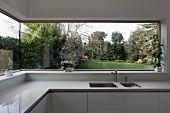 Panoramafenster mit Blick in den Garten in heller Designer-Küche aus Corian – Bild kaufen – living4media