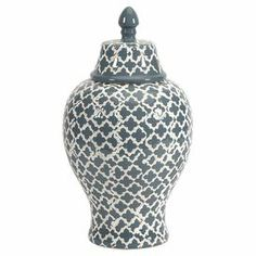 "Blue ceramic urn with a white quatrefoil motif.  Product: UrnConstruction Material: CeramicColor: White and blueDimensions: 14"" H x 7.5"" Diameter"