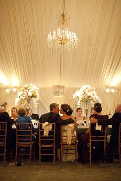 beautiful lighted tent with fabric and tall flowers