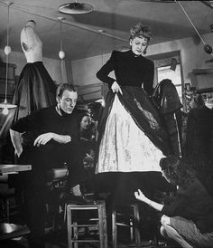 1951  Jacques Fath watches as the tailor hems loose ends at the bottom of a dress. / Photographed by Nina Leen.  -LIFE photo archive