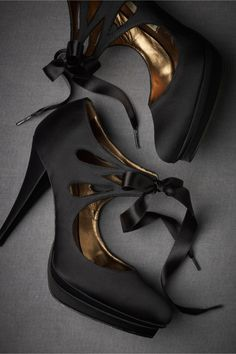 "Bombshell Booties  Bombshell Booties -Curves, cut-outs, and satin bows make up Pura Lopez's come-hither heels. This pair comes with both white and black ribbons, for you to customize your look. Tie closure. Satin upper; leather sole. 4.5"" satin wrapped heel. Spain."