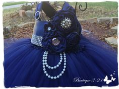 My production time is 3-4 weeks. Rush Orders are sometimes available. Contact me for details.  This listing is for my Party Style tutu dress. This dress comes with a variety of flowers on one side with embellishment buttons, hanging pearl strands and a strand of rhinestones and a shoulder rhinestone buckle. Wide satin side ribbon (helps hide the crochet top) and wide satin shoulder straps. These straps are combined in the back turning into a big bow in the back. This dress is great for any…