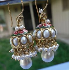 Jadau Jhumkas - Jaipur Jhumkas  Jadau - is the art of setting gemstones/pearls, then Kundan(pure 24 Karat gold is poured to fill the gap in between the stones and the jhumka, these jhumkas usually also have meenakari work done.
