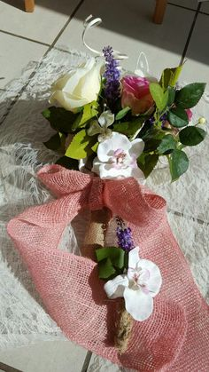 Pretty pastel colours in this bridal wedding bouquet are perfect for the spring. Rustic hessian, chunky bows and a butterfly bopper add a touch of fun. Bouquet and buttonhole available with Bridal Box Studios.