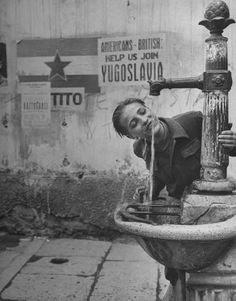 Nat Farbman, A boy getting a drink from a water fountain, Yugoslavia, May 1946.