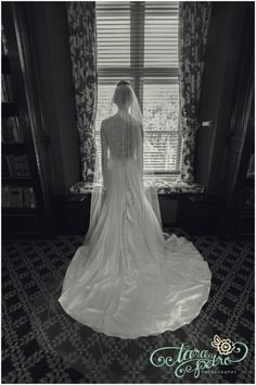 Bride gazes out window wearing jaw-dropping wedding gown with cathedral-length veil & extensive train // johnparkerbands.com