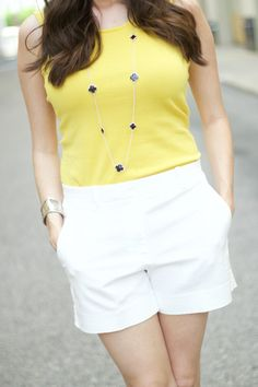White Tailored Shorts with Yellow Sleeveless Top and Silver Chain Necklace. Casual, colorful summer outfit