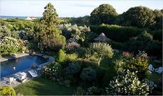 The Atlantic is very close. Here you can see into the walled garden and the little thatched house. Tennis courts are right behind the pool, hidden by bushes. Grey Gardens House, Gray Gardens, Thatched House, Thatched Roof, Hamptons House, The Hamptons, Los Kennedy, Rose Of Sharon, Lily Pond