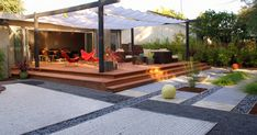 Defined backyard living space: pea gravel walkways, sand (or sod/grass), river rock creek bed for drainage