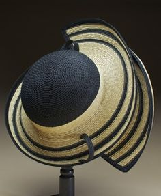 Pappillon Description: Natural braided wheat straw is stitched together with black synthetic straw, to make a brim and a crown. These are blocked on handmade molds, then joined, and finished with wire, hemp binding and cotton belting. Dimensions: H:8.00 x W:20.00 x D:20.00 Inches