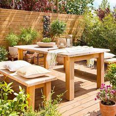 Terraza con comedor exterior con mesa, banco, suelo y pared de madera, y plantas