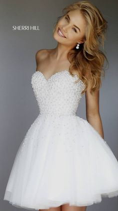 Live your romantic dreams in the absolutely divine Sherri Hill 11312 short dress. This strapless tulle gown showcases a delicately beaded bodice, with sweetheart neckline and semi-open back. The A-line skirt flares from the natural waistline in tantalizing layers of dreamy tulle, gorgeously accented with scattered beads.