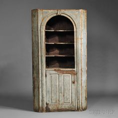 Blue-painted Pine Corner Cupboard, probably New Hampshire, mid-18th century, the arched and molded opening centering a molded panel with three shaped shelves and a base shelf, above a hinged door with two fielded panels, original robin's egg blue-painted surface, (imperfections), ht. 84 1/2, wd. 47, dp. 18 1/2 in.