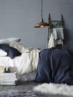 déco chambre cocooning, mur gris, linge de lit blanc et bleu marine, parquet gris, echelle decorative bois, suspension industrielle