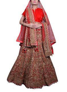Saroj Jalan brings to you a stunning orange and pink lehenga. The alluring raw silk orange lehenga features red patchwork adorned with golden embroidery on top and embellished red and pink borders. It has been teamed with a red fully zardosi embroidered blouse with orange scalloped border at the sleeves. Adding further charm is the red stole with all over buti design. It also includes an orange net dupatta with a pink and red scalloped border.
