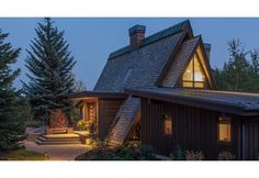 View of the approach and entry at twilight.  A contemporary A-Frame remodel.  Rainscreen wood siding, board and batten siding, bonderized standing seam roof, and green copper flashing.