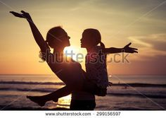 Mother and daughter playing on the beach at the sunset time. Concept of friendly family