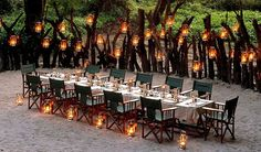 Wedding reception in the sand. Love the encircling wood and safari chairs.