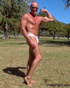a older muscle man body builder flexing outside