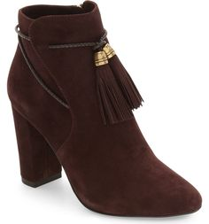 Slender braided cording encircles the ankle of this luxe leather bootie with two gleaming capped tassels. An almond toe and a wrapped half-moon heel add a polished finish.