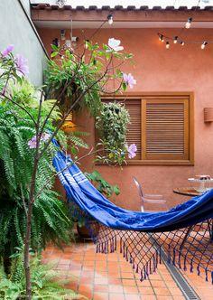 Área externa tem rede de balanço e muitas plantas pendentes nas paredes.