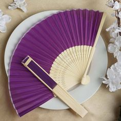 Asian Silk Folding Fans - Purple | eFavorMart / Add a classical Asian touch to your wedding, or a special event by presenting your esteemed guests with this special souvenir. Our stylish silk wedding hand fan is intricately handcrafted with a bamboo structure. The framing and spines are crafted from hand-picked bamboo and durably glued with a seamless cut piece of silk to fashion this immaculate magnum opus. Give these swish fans to your respected guests and let them create the lasting…