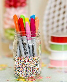 A jar full of sprinkles is a colorful place to store pens.