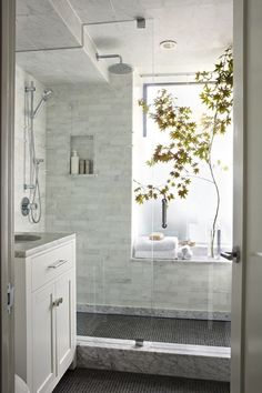 Beautiful tiled shower in white/gray with rainshower head. Love the light coming from the frosted window in the shower letting in light and the window seat which provides a shelf.