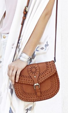 Vintage-inspired crossbody saddle bag with intricate laser cut detailing and fold-over snap closure. Easy weekend and Coachella festival bag.