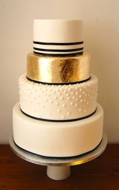 A modern gold leaf and white dot wedding cake