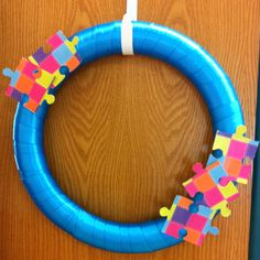 DIY Autism Awareness Wreath. Wreath form, blue ribbon, scrapbook paper, old puzzle pieces, and modge podge!