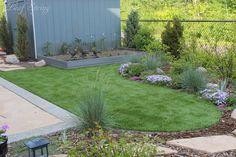 Backyard retreat with synthetic lawn, aluminum edging, vegetable garden and perennial shrub border.