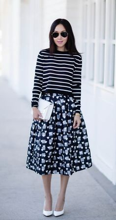Print on print action with a striped sweater and pleated midi skirt.