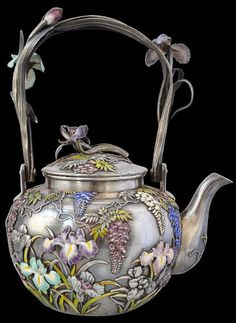 View 6: Arguably, this remarkable silver and enamel tea set is among the finest of its type ever made. It comprises a teapot, a creamer, a lidded sugar bowl and a pair of sugar tongs. Each is overlaid in various coloured cloisonne enamels with complex and highly naturalistic iris and wisteria blooms and foliage. The feathery fine wisteria leaves alternate between light green enamel and silver; the blooms between blue, mauve and cream. The iris blooms and buds are in pale green, mauve, cream…