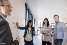 Stock Photo : Smiling architects discussing plans at wall