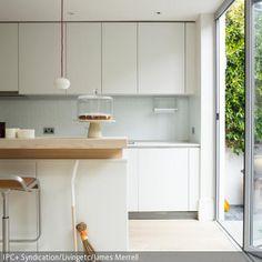 Eine Küchenarbeitsplatte aus Holz setzt einen natürlich schönen Kontrast zu einer weißen Küchenfront. Einzelne Accessoires, wie ein Reisigbesen oder eine gläserne …
