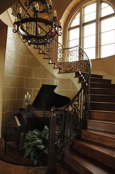 Stunning grand foyer ... wood steps, wrought iron railing, iron chandelier, baby grand piano.