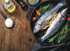 #Ingredients for cookig fish dinner  Ingredients for cookig healthy fish dinner. Raw uncooked seabass fish with rice olive oil lemon slices herbs and spices on black grilling iron pan over rustic wooden background top view copy space horizontal composition