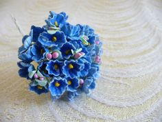 A sweet little bouquet of VINTAGE forget-me-nots in aged denim blue flocked paper - made in Korea over 60 years ago. Each bunch measures just under 5 in length and comes with 8 wired stems - each with 5 mixed flowers on it - for a total of 40 flowers.