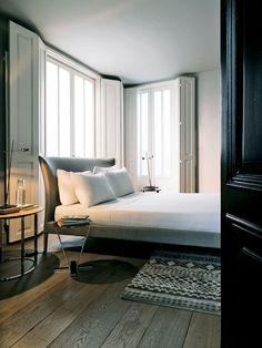 【ELLE DECOR】 ナイトテーブルとリネンが整えられたベッドは「Maxalto」、カーペットは「ナニ・マルキナ」、照明はドイツの「Absolut Lighting」社のもの。
