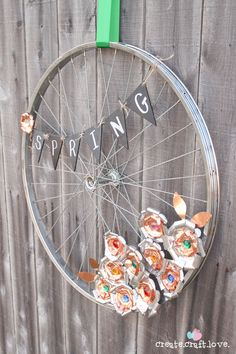 Make a springtime wreath for your backyard with an old bicycle wheel and cut-up soda cans.